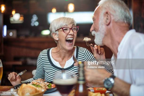 senior woman laughing while feeding her male partner in the restaurant - restaurant stock pictures, royalty-free photos & images