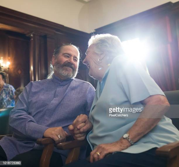 senior woman laughing with preacher - congregation stock pictures, royalty-free photos & images