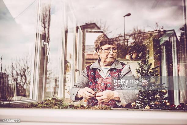 Senior  Woman Laying down Moss for Nativity Scene, Balcony, Europe