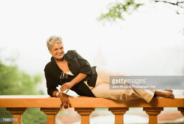 Senior woman laying on balcony railing