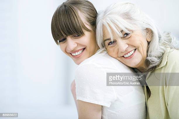 senior woman leaning against adult daughter's back, smiling at camera - three quarter front view stock pictures, royalty-free photos & images