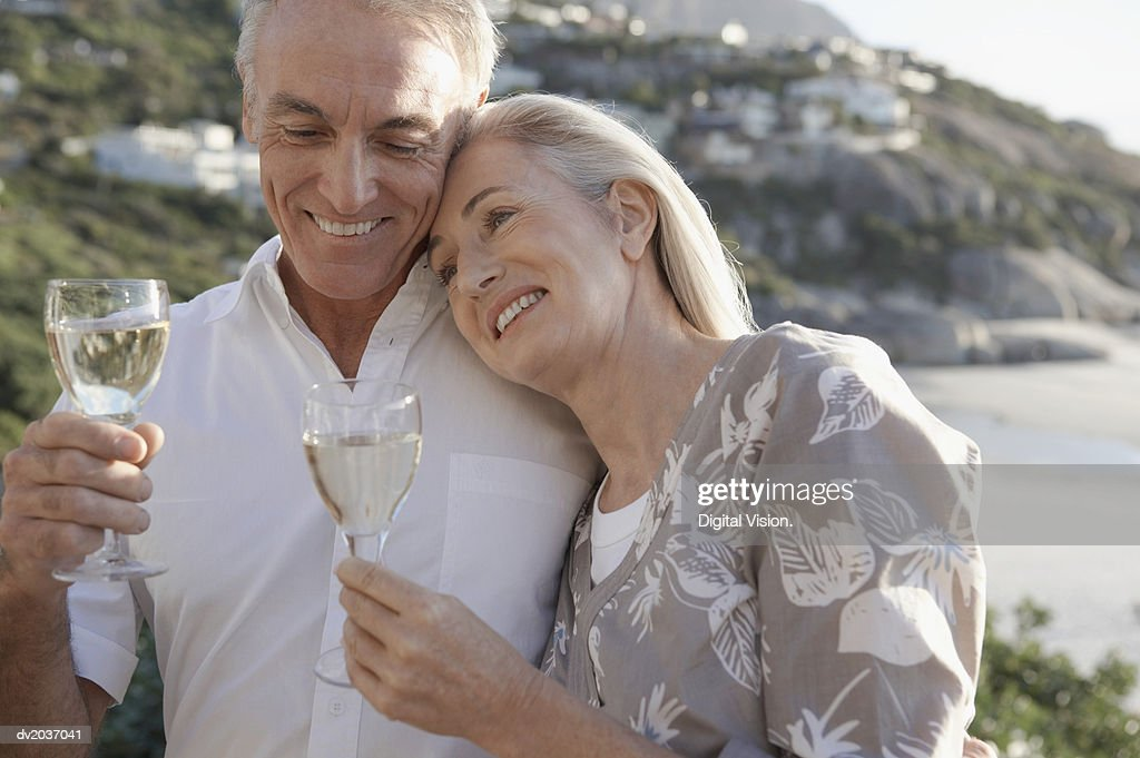 Senior Woman Leaning Against the Shoulder of a Senior Man on a Beach : Stock Photo