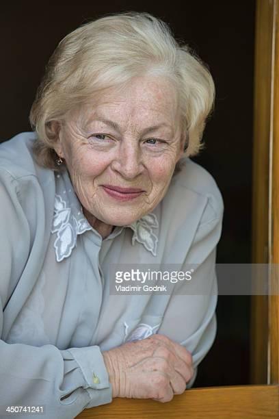a senior woman leaning on a window sill, smiling while looking away - eine seniorin allein stock-fotos und bilder