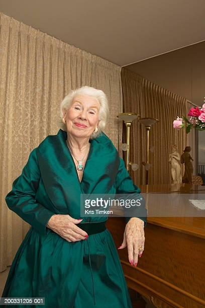 senior woman leaning on piano, smiling, portrait - eine seniorin allein stock-fotos und bilder