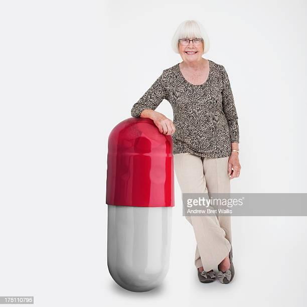 Senior woman leans on a giant pill capsule