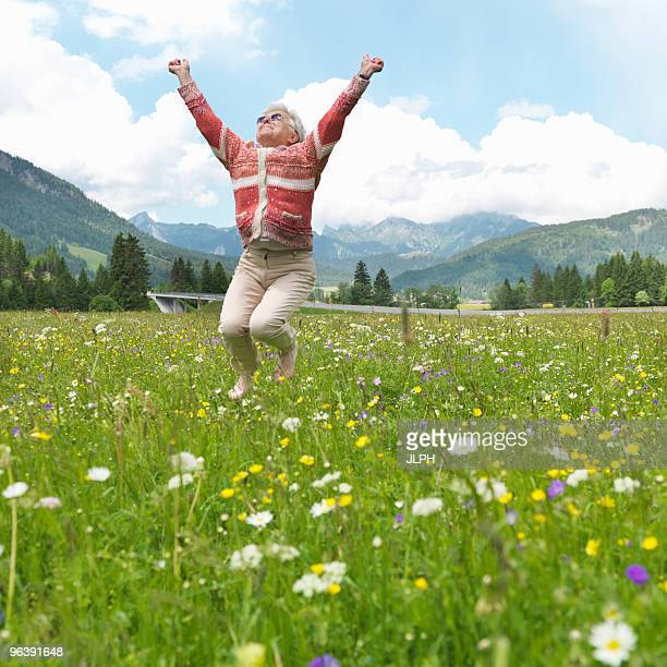 Senior woman leaping in field of flowers