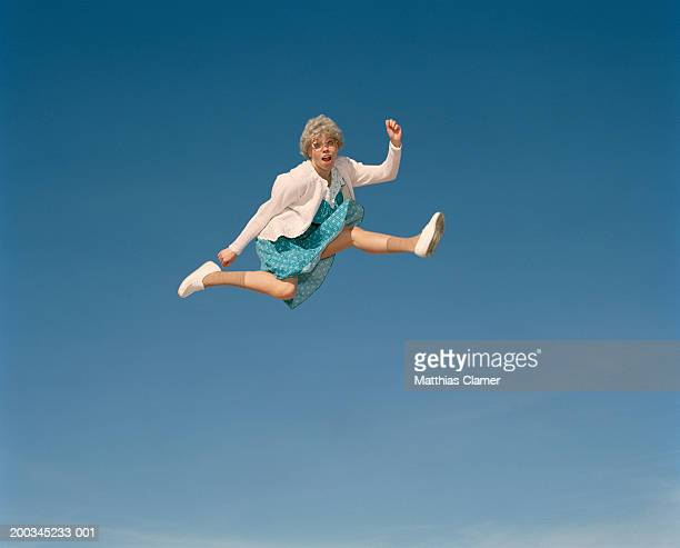senior woman leaping in mid air, portrait - old lady funny stock pictures, royalty-free photos & images