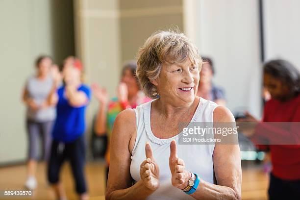 Senior woman learning dance move at senior center