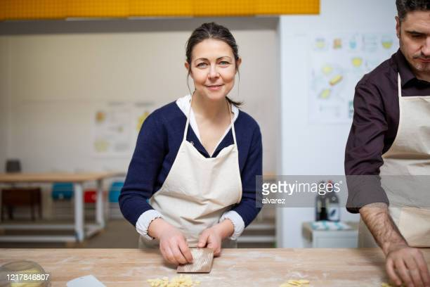 senior woman learning making fresh pasta at cooking class - instructor stock pictures, royalty-free photos & images
