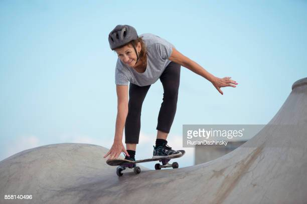 新しい何かを学ぶ、屋外の極端なスポーツをしている年配の女性。 - ハーフパイプ ストックフォトと画像