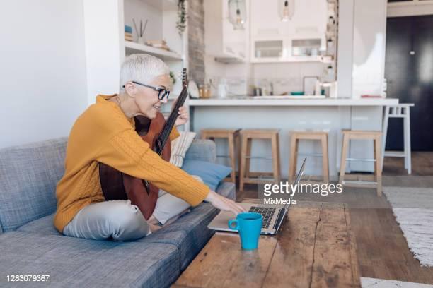 seniorin lernt gitarre online spielen - 55 59 jahre stock-fotos und bilder