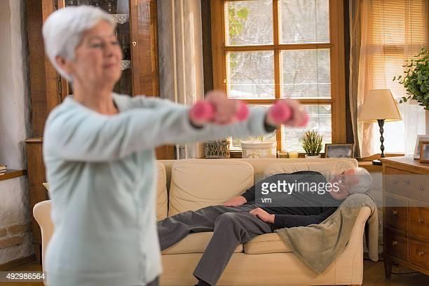 Donna anziana sollevamento pesi nel soggiorno, marito notte