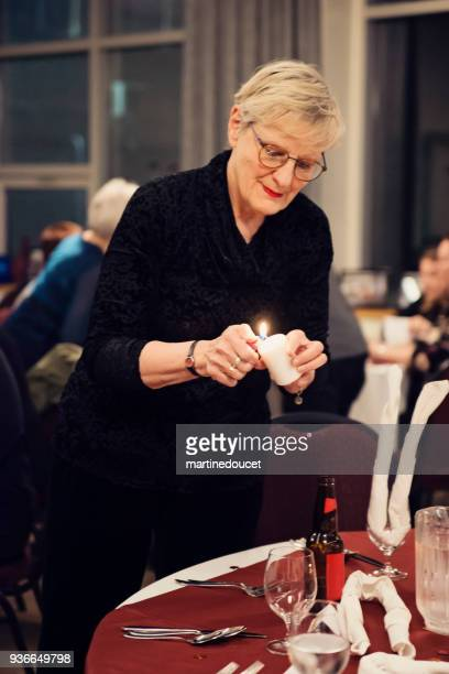 """senior woman lighting a candle in celebration dinner. - """"martine doucet"""" or martinedoucet stock pictures, royalty-free photos & images"""