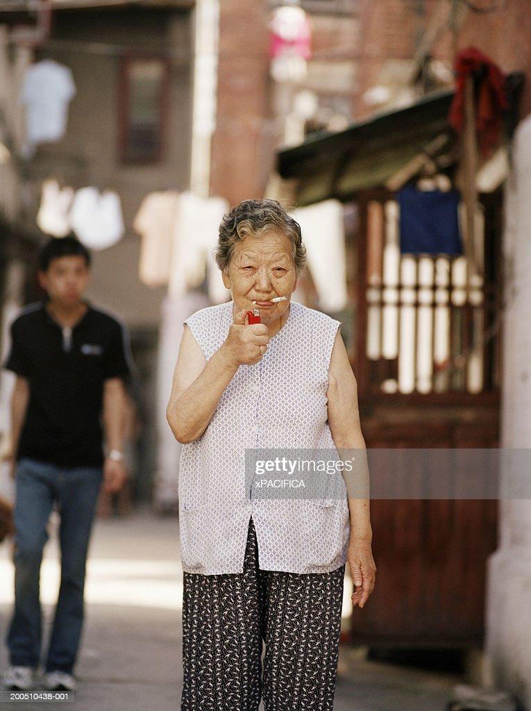 Senior woman lighting cigarette : Stockfoto