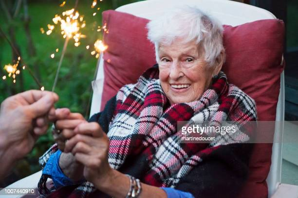 """senior woman lighting sparklers outdoors at dusk. - """"martine doucet"""" or martinedoucet stock pictures, royalty-free photos & images"""