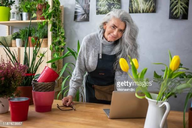 hogere vrouw als haar installaties - alleen één seniore vrouw stockfoto's en -beelden