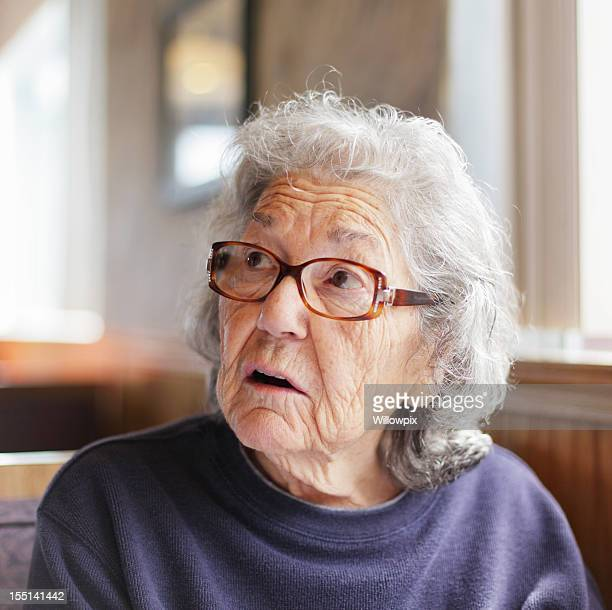 Senior Woman Listening in Restaurant