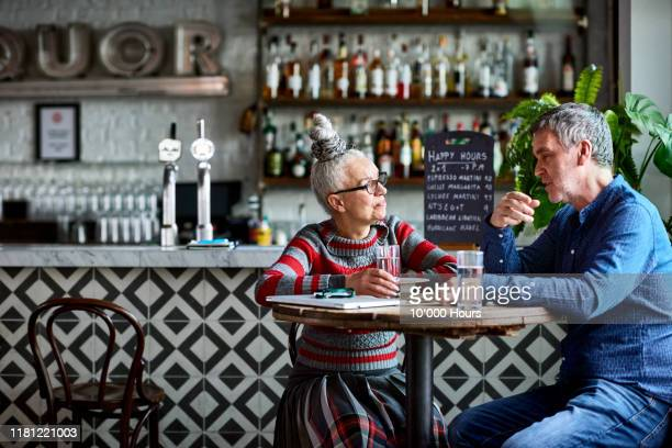 senior woman listening to colleague in cafe - restaurant stock pictures, royalty-free photos & images