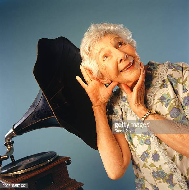 senior woman listening to music from gramophone - gramophone stock pictures, royalty-free photos & images