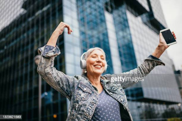 senior woman listening to music on wireless headphones - 60 64 years stock pictures, royalty-free photos & images