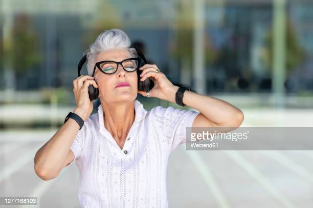 senior woman listening to music through headphones against glass window - one senior woman only stock pictures, royalty-free photos & images