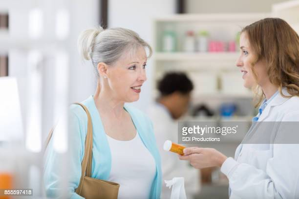 Senior woman listens as pharmacist consults with her about her prescription