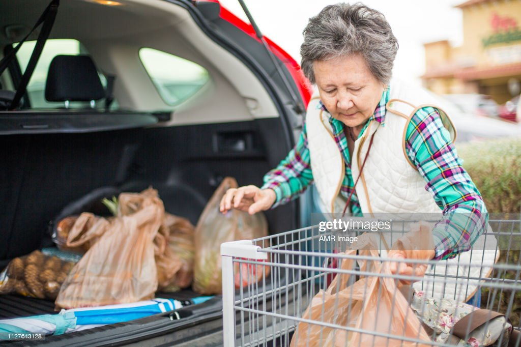Senior woman loading grocery bags to her car. : Stock Photo