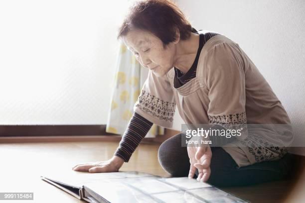年配の女性が自宅で写真アルバムを探して