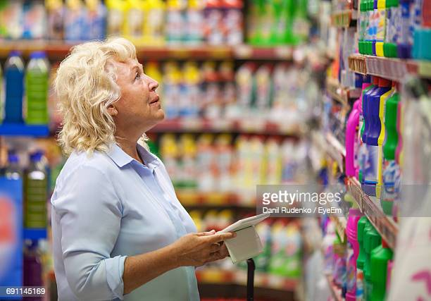 Senior Woman Looking At Cleaning Product On Rack In Supermarket