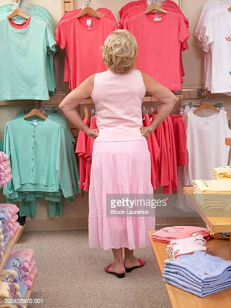 Senior woman looking at clothes in store, rear view