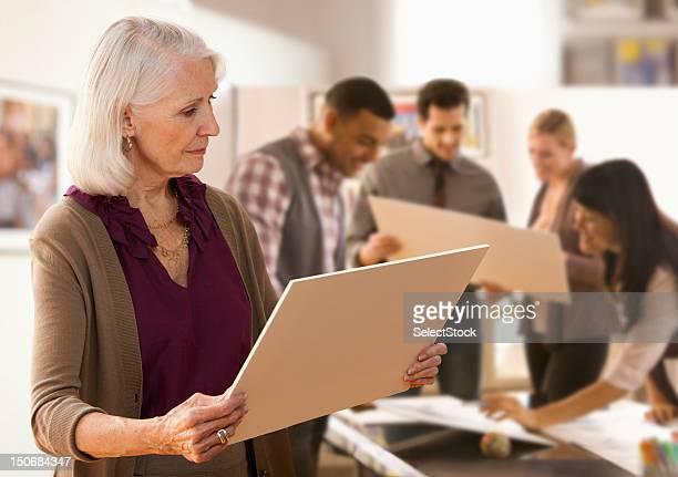 Senior Frau auf der Suche in designs mit Kollegen
