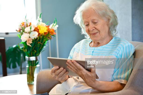 senior woman looking at digital tablet in house - izusek stock pictures, royalty-free photos & images