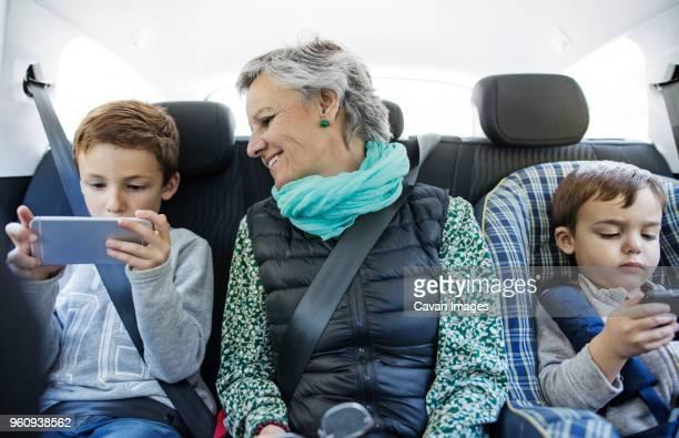 Senior woman looking at grandson using smart phone in car