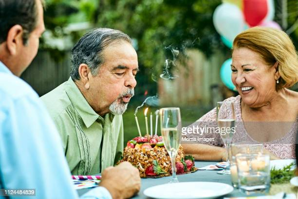 senior woman looking at man blowing candles - celebration fl stock pictures, royalty-free photos & images