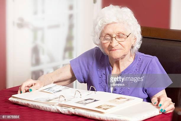 Senior Woman Looking At Old Photo Album