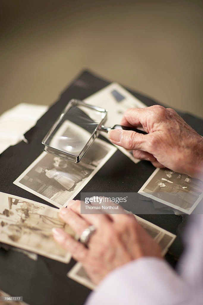 Senior woman looking at old photographs in album through magnifying glass, close-up of hands : Stock Photo