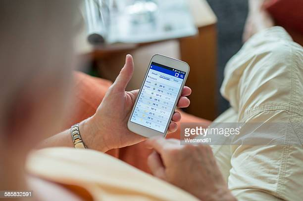 Senior woman looking at weather forecast on smartphone display