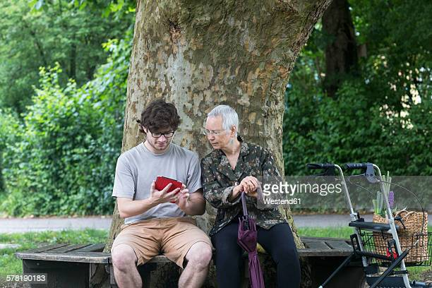Senior woman looking at young man with digital tablet on park bench