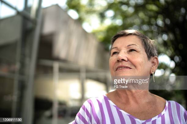 senior woman looking away outdoors - hope stock pictures, royalty-free photos & images