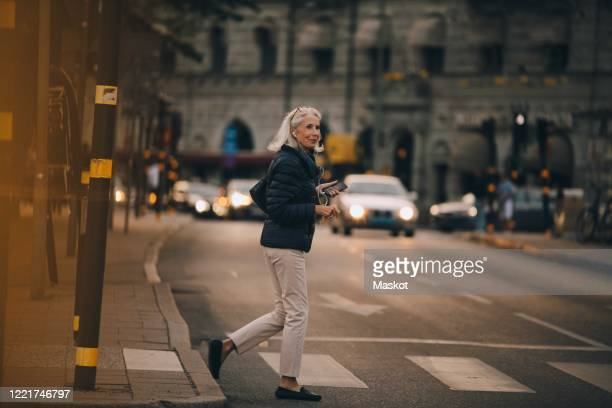 senior woman looking away while crossing road in city - crossing stock pictures, royalty-free photos & images
