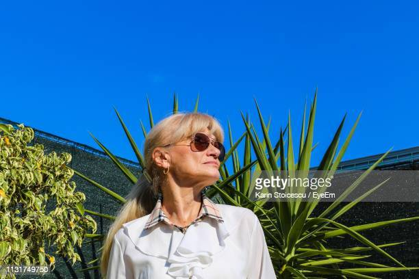 Senior Woman Looking Away While Standing Against Clear Blue Sky During Sunny Day