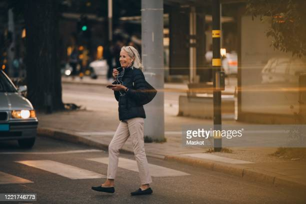 senior woman looking away while walking on zebra crossing in city - animated zebra stock pictures, royalty-free photos & images
