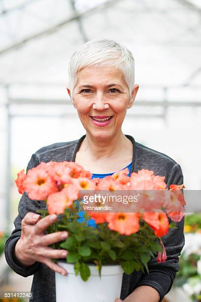 Senior woman looking for flowers at garden center