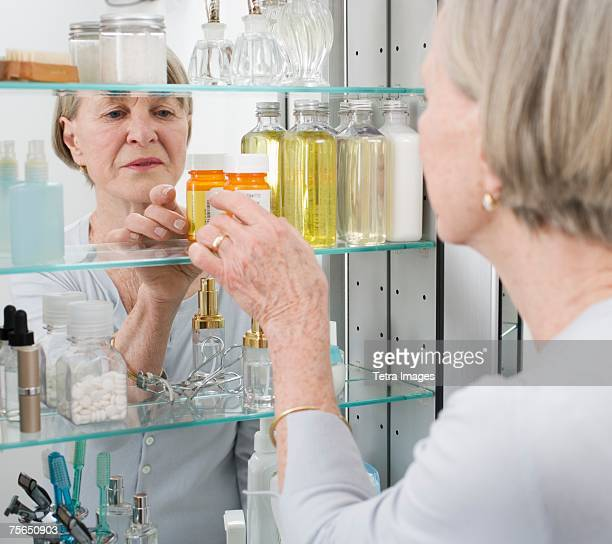 senior woman looking in medicine cabinet - medicine cabinet stock pictures, royalty-free photos & images