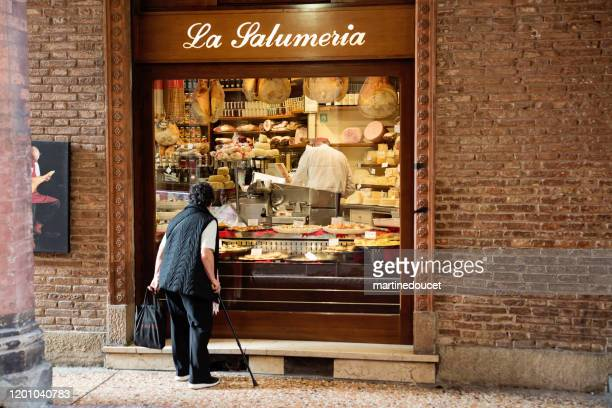 senior woman looking in the window of a salumeria in bologna, italy. - emilia romagna stock pictures, royalty-free photos & images
