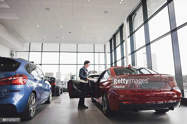senior woman looking inside car in showroom - new stock pictures, royalty-free photos & images
