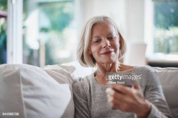 senior woman looking on cell phone at home - seniore vrouwen stockfoto's en -beelden