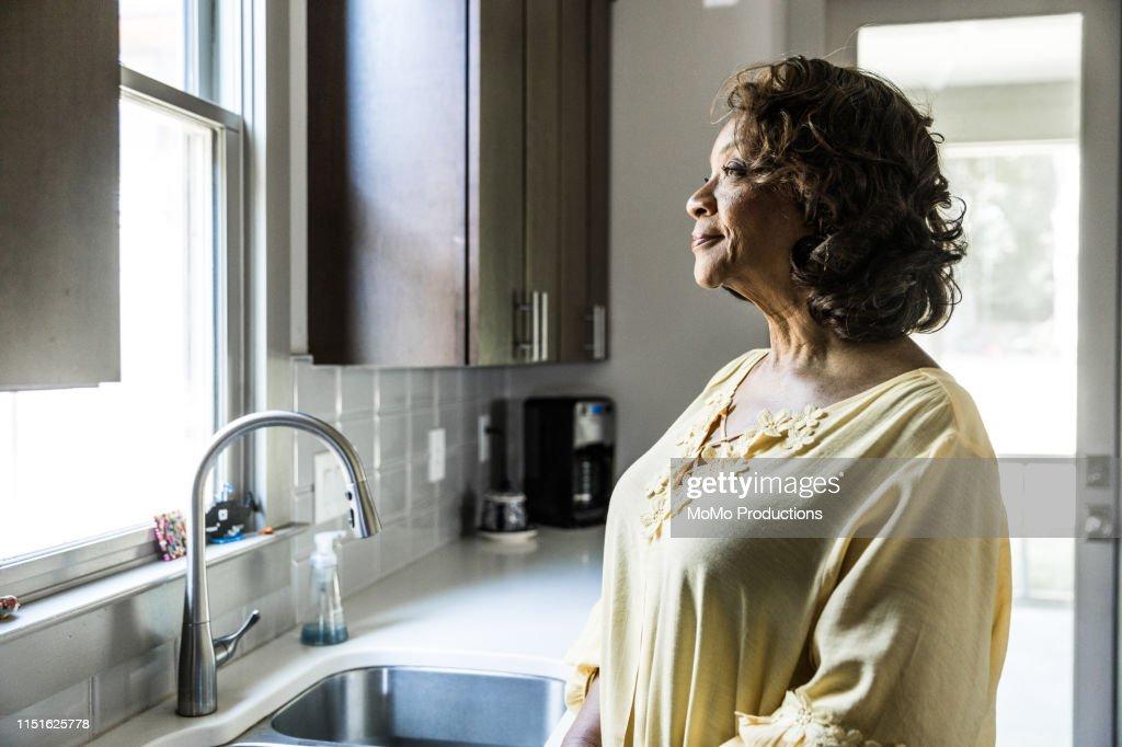 Senior woman looking out kitchen window : Stock Photo