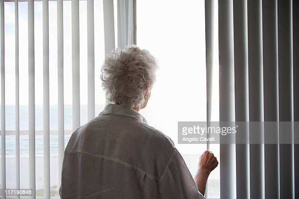 senior woman looking out of a window - alleen één seniore vrouw stockfoto's en -beelden