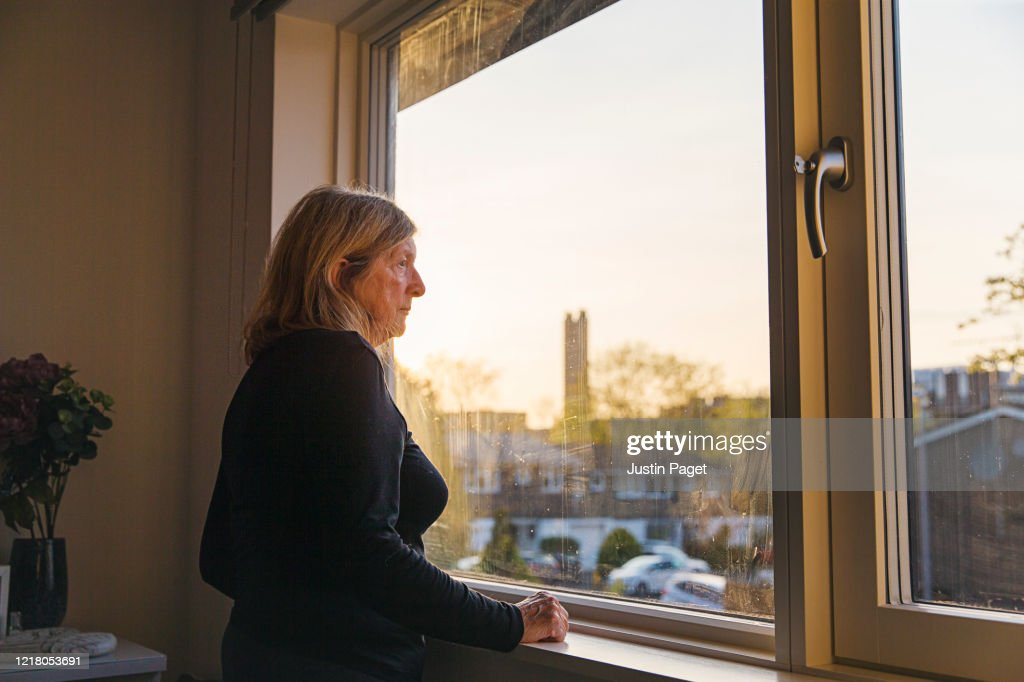 Senior woman looking out of her bedroom window at sunset : Stockfoto